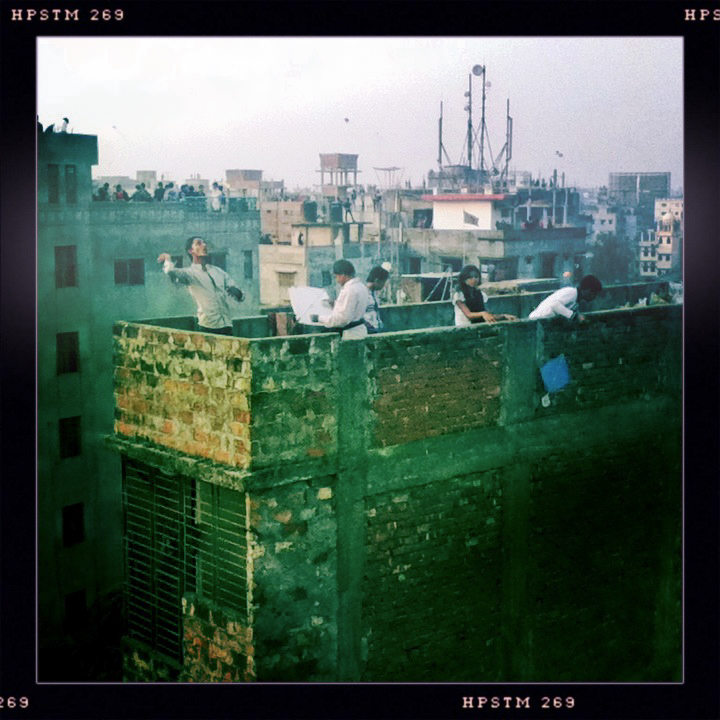 15th Jan 2012. Old Dhaka, Dhaka, Bangladesh. Cityscape  of Old Dhaka with people standing on the roofs of buidlings and raising kites in the air. The kite festival is a Hindi festival. Raising the kites is a symbol for wellcomming the Spring Photograph by Evi Lemberger/Drik